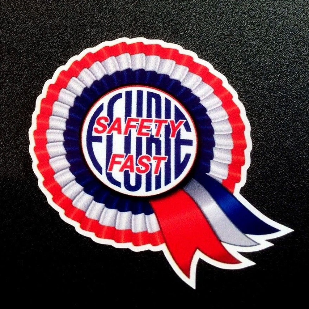 A red, white and blue BMC rosette. Centre of the rosette is Safety Fast in red lettering overlaying Ecurie in blue lettering.