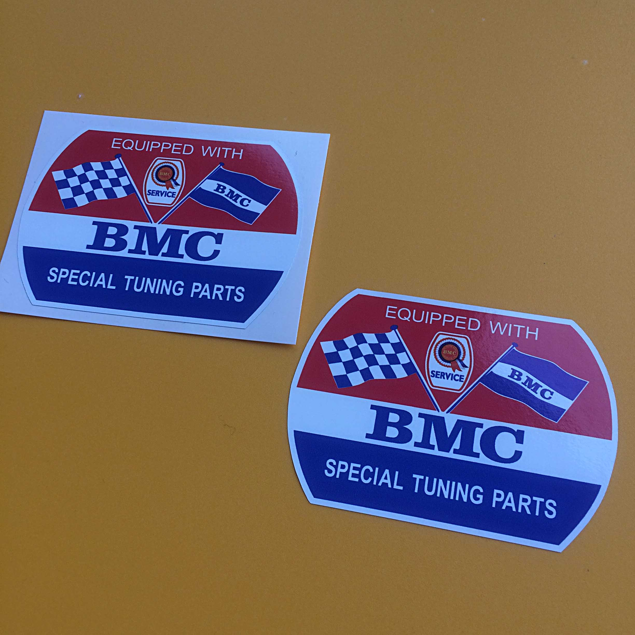 The lettering Equipped With BMC Special Tuning Parts on a red, white and blue background. Additional images are chequered and BMC crossed flags. Also BMC rosette with the word Service below.