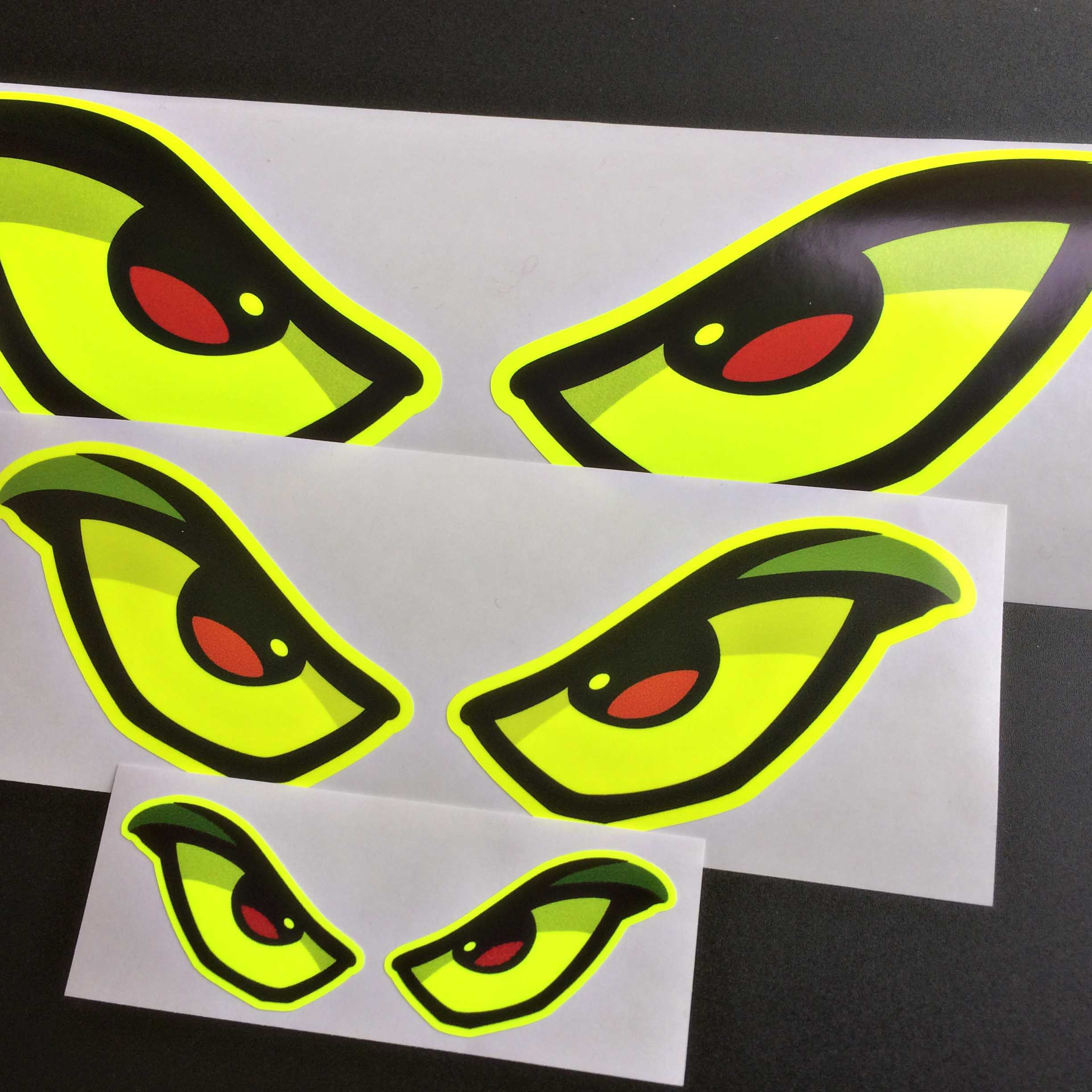 Pair of reflective, fluorescent yellow evil eyes. Pupils are black and red. Eyes are lined in thick black liner.