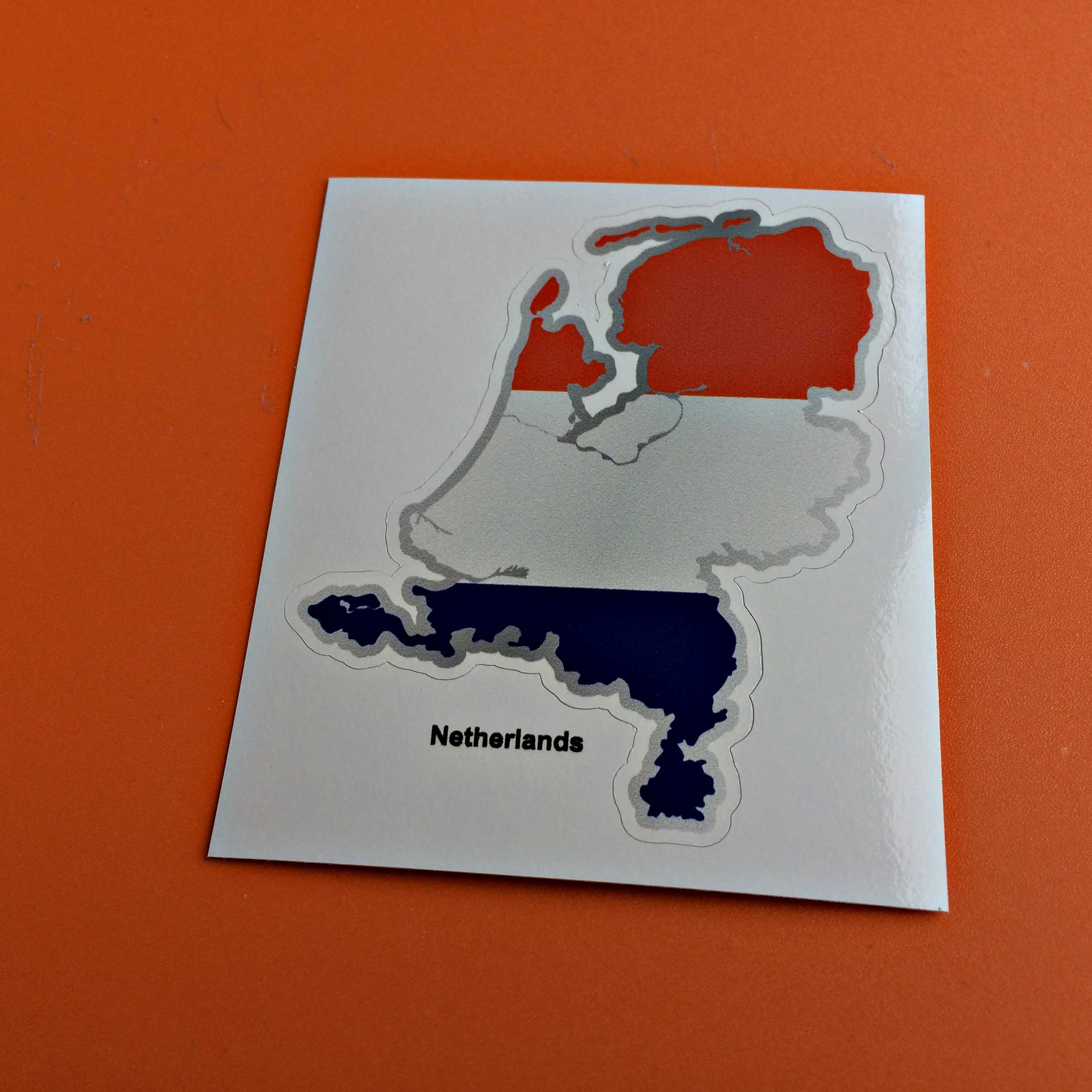 Netherlands flag and map with Netherlands in black lettering below. Flag is a horizontal tricolour of red, white and blue.