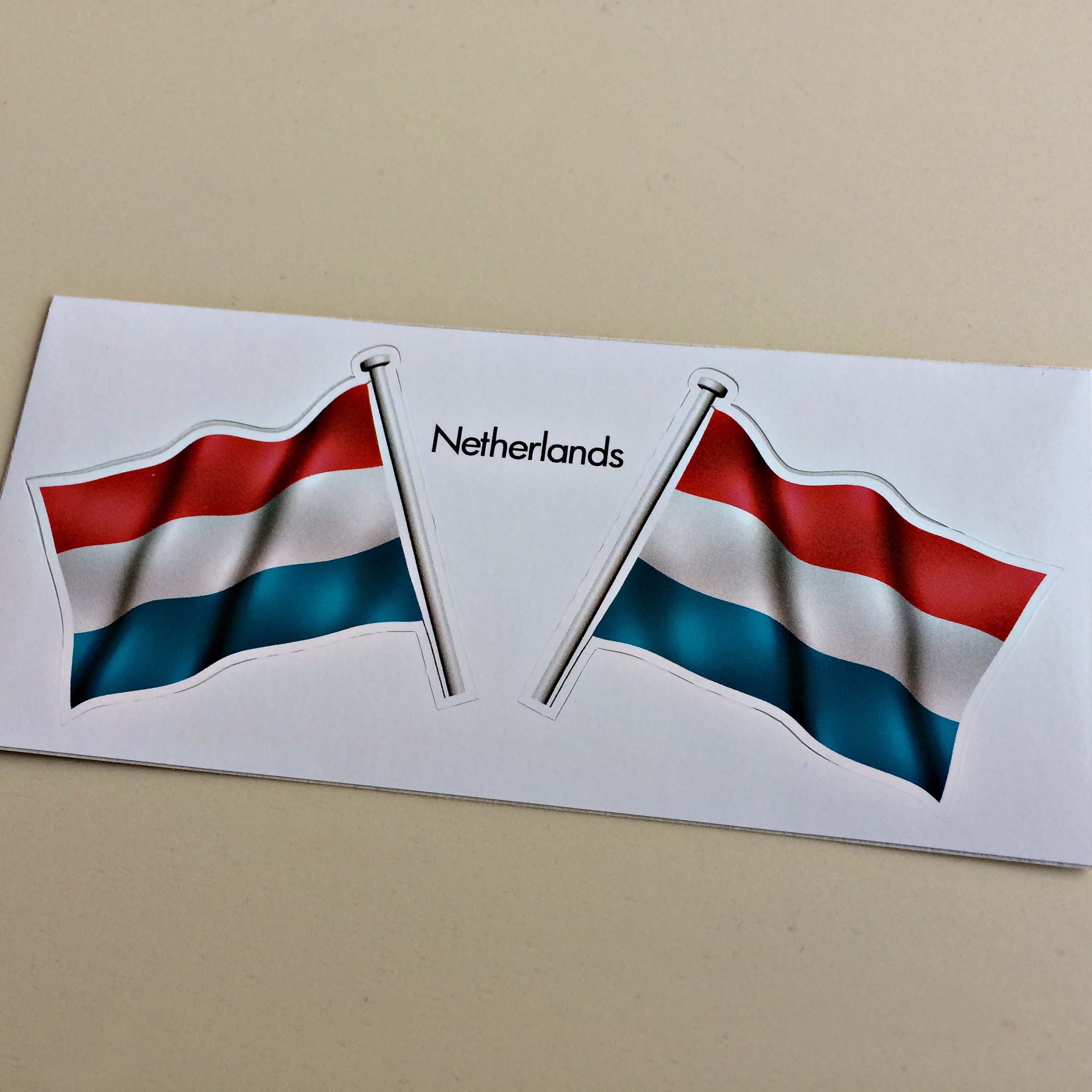 Two wavy flags on poles with Netherlands in black lettering in-between. The flag is a horizontal tricolour of red, white and blue.