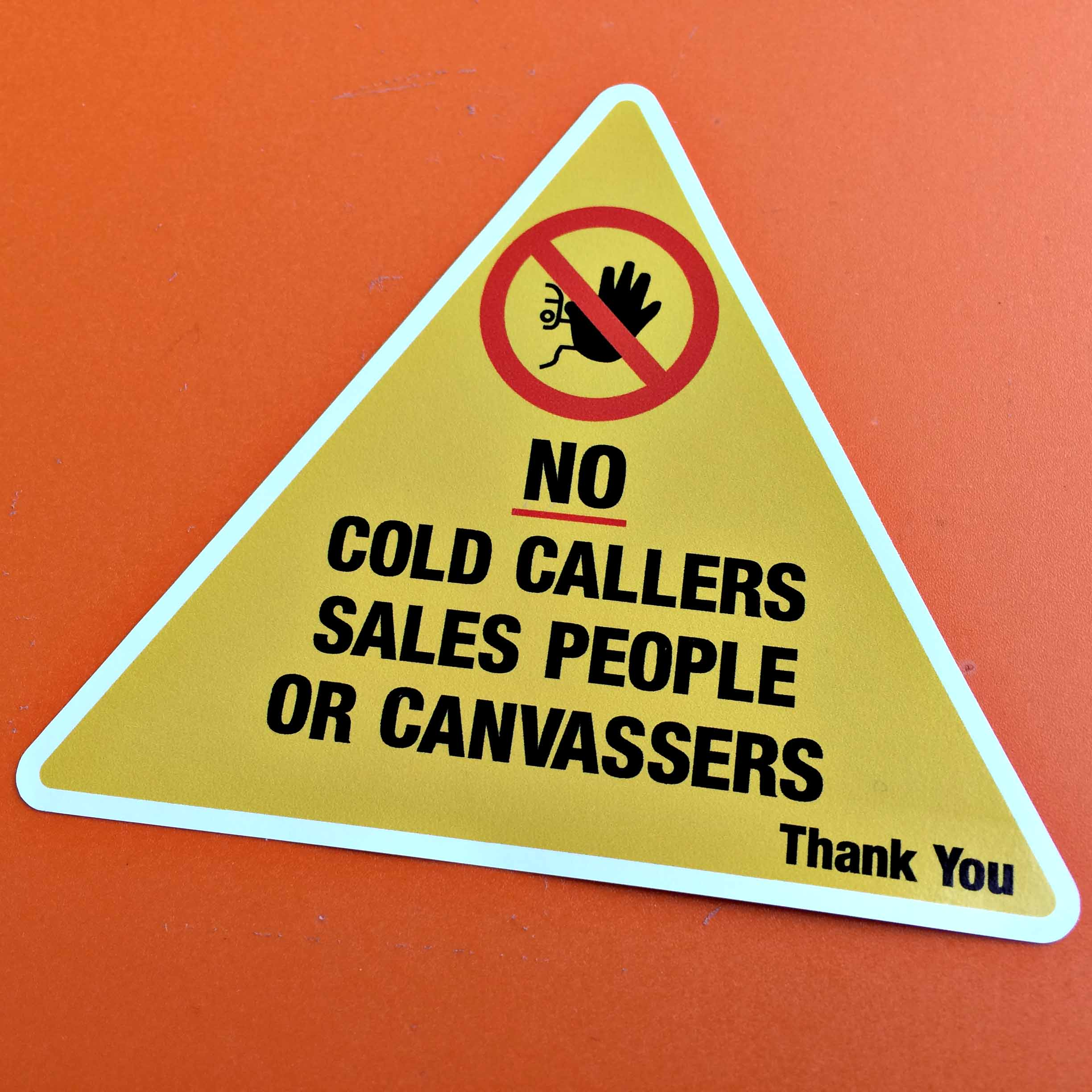 Yellow triangle. In black letters No cold callers sales people or canvassers. Thank You. Above is a prohibition sign.