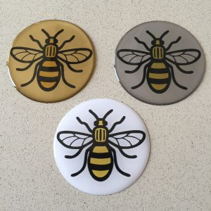 Black and yellow bee on a round, domed sticker.