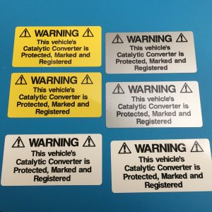 Catalytic Convertor Warning Stickers. Black text on either a yellow, white or silver background. With the word Warning in bold capital letters. The rest of the text 'This vehicle's Catalytic Converter is Protected, Marked and Registered' in lower case.
